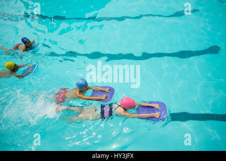 High angle view of girls and boys using kickboard while swimming in pool - Stock Photo