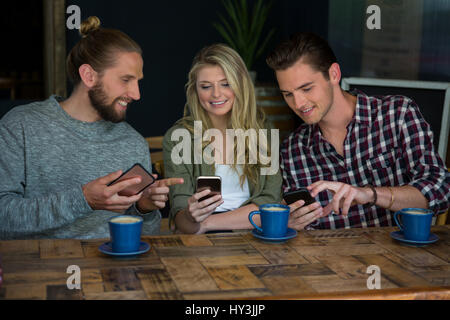 Smiling young friends using smart phones at table in cafe - Stock Photo