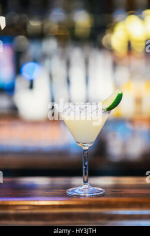 Glass of Classic Margarita Cocktail with a Wedge of Lime - Stock Photo