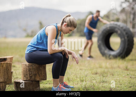 Tired fit sitting on tree trunk in boot camp - Stock Photo