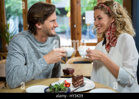 Smiling young couple having coffee at table in cafeteria - Stock Photo
