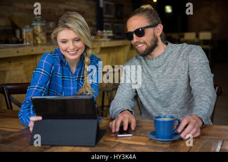Smiling young couple using tablet computer at table in cafeteria - Stock Photo