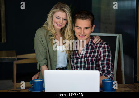 Smiling young couple using laptop at table in coffee shop - Stock Photo