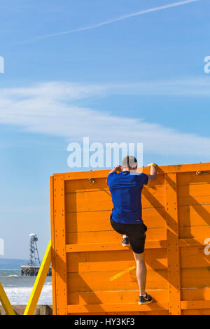 Climbing over the cliffhanger obstacle, part of the Sandstorm Beach Challenge, on Bournemouth beach, a beach assault - Stock Photo