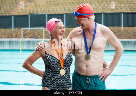 Cheerful senior couple wearing medals while standing at poolside - Stock Photo