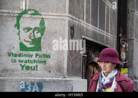 BELGRADE, SERBIA - NOVEMBER 7, 2014: Old woman passing by a pro Russian graffiti (Vladimir Putin is watching you) - Stock Photo