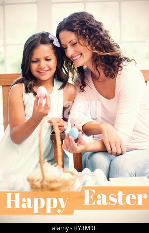 Happy mother and daughter holding easter eggs  against happy easter logo - Stock Photo