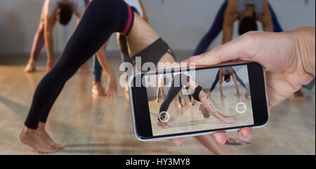 Hand holding mobile phone against white background against woman performing downward facing dog pose - Stock Photo