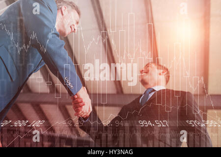 Stocks and shares against happy businessmen shaking hands - Stock Photo