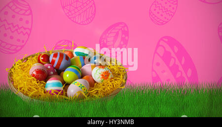 Multi colored easter eggs in wicker basket against pink background - Stock Photo