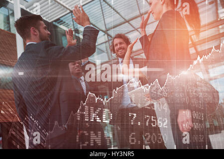 Stocks and shares against group of happy businesspeople giving high five to each other - Stock Photo