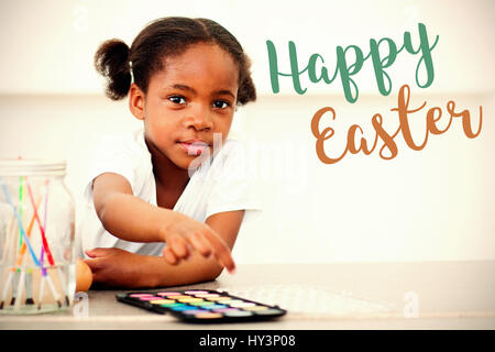 Easter greeting against cute little girl painting eggs in the kitchen - Stock Photo