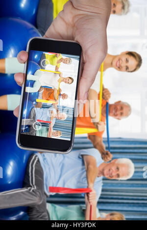 Hand holding mobile phone against white background against portrait of seniors using exercise ball and stretching - Stock Photo