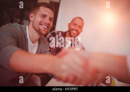 Happy business people shaking hands in creative office - Stock Photo
