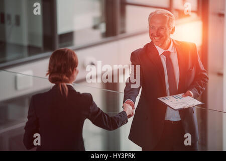 Businessman shaking hands with colleague in office - Stock Photo