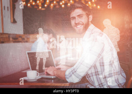 Shiny silhouettes on blue background against young man working on his computer - Stock Photo