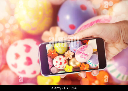 Hand holding mobile phone against white background against painted easter eggs with different designs - Stock Photo