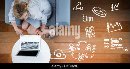 Woman on her laptop against wooden floor - Stock Photo