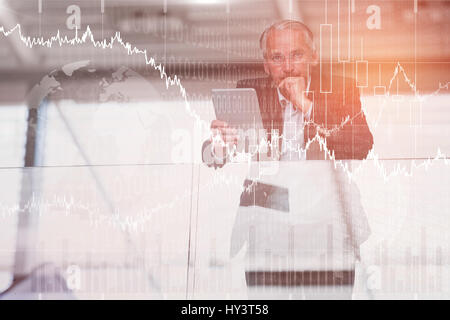 Stocks and shares against serious businessman holding digital tablet - Stock Photo