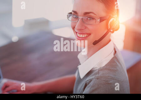 Close-up view of happy businesswoman with headset in call center - Stock Photo