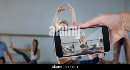 Hand holding mobile phone against white background against portrait of woman performing stretching exercise - Stock Photo