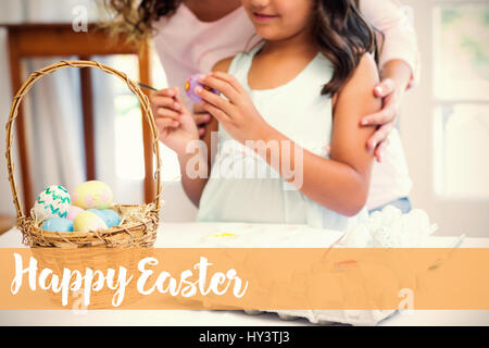 Happy mother and daughter painting easter eggs  against happy easter logo - Stock Photo
