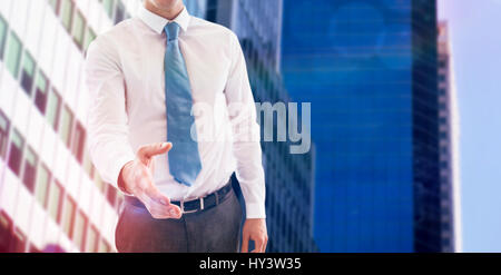Smiling businessman offering handshake against low angle view of skyscrapers - Stock Photo