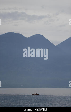 Fisherman on his own crafted built wooden boat in lake in Lake Atitlan Guatemala - Stock Photo