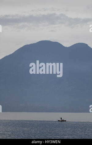 Fishing in an ancient Mayan design boat in Lake Atitlan - Stock Photo