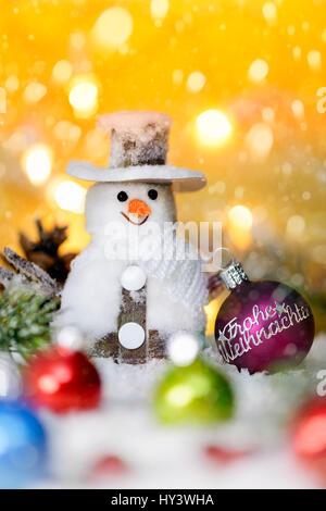 Christmas ball with label glad Christmas and snowman, Weihnachtskugel mit Aufschrift Frohe Weihnachten und Schneemann - Stock Photo