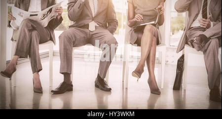 Business people sitting on chairs in office - Stock Photo