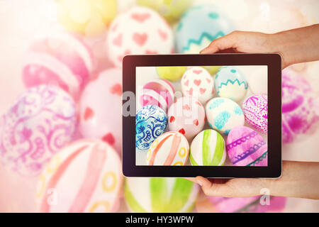 Close-up of hands holding digital tablet against painted easter eggs on white background - Stock Photo