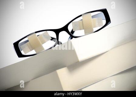 Glasses with paving on book pile, educational strike, educational plight, Brille mit Pflastern auf Bücherstapel, - Stock Photo