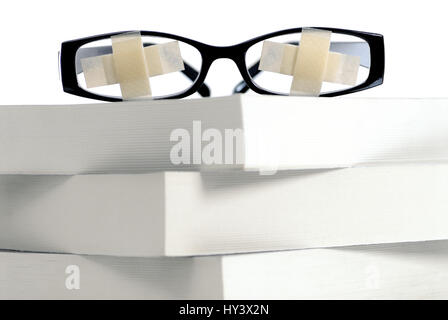 Glasses with paving on book pile, educational strike, educational plight, Brille mit Pflastern auf Buecherstapel, - Stock Photo