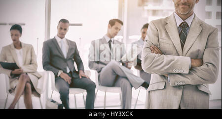 Serious businessman standing in  front of business people in office - Stock Photo