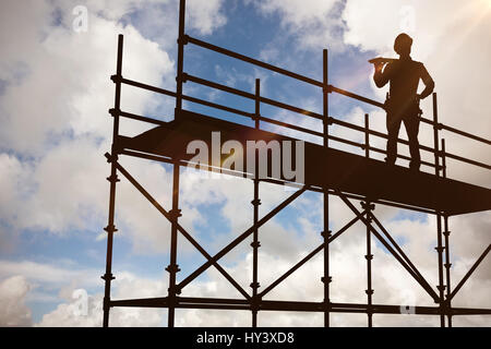Thoughtful worker carrying wooden planks against blue sky with white clouds - Stock Photo