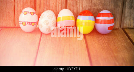 Painted Easter eggs arranged side by side on wooden table - Stock Photo