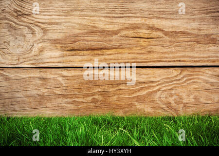 Grass against brown wood panelling - Stock Photo