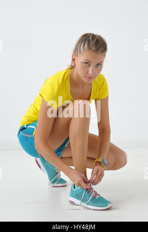 Young and pretty fitness instructor tying a loose lace on sneakers - Stock Photo