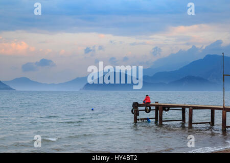Lonely woman sitting on pier during sunset in marmaris, turkey - Stock Photo