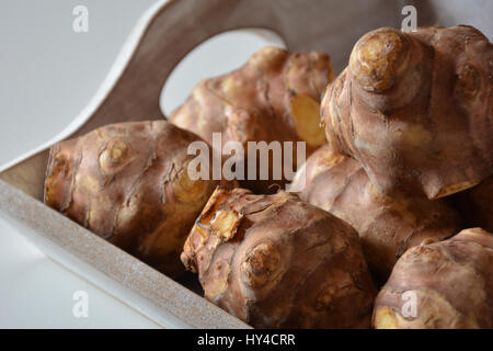 Closeup view of raw Jerusalem artichokes in a wooden box - Stock Photo