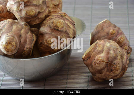 Closeup view of raw Jerusalem artichokes in a stainless steel bowl - Stock Photo