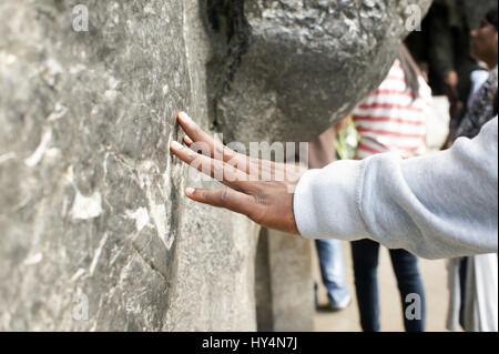 A pilgrim touches the stone wall of the Grotto of Massabielle, in Lourdes, France, visiting a holy spring that is - Stock Photo