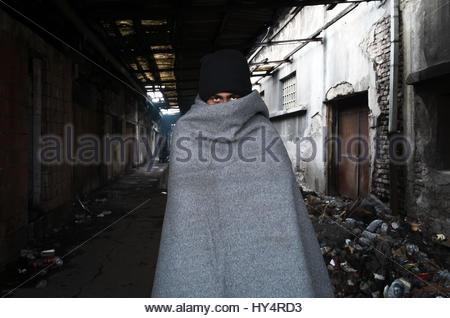 BELGRADE-INFORMAL REFUGE CAMP-JAN 2017— Hazrat, 16, an Afghan refugee, warms himself at a fire behind the main train - Stock Photo
