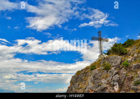 Cross on mountain with cloudy blue sky in background - Stock Photo