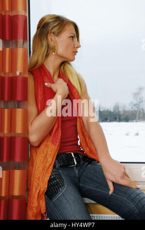Young woman looks sadly from the window, Junge Frau guckt traurig aus dem Fenster - Stock Photo
