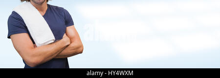 Portrait of a smiling handsome trainer with arms crossed standing in the gym - Stock Photo