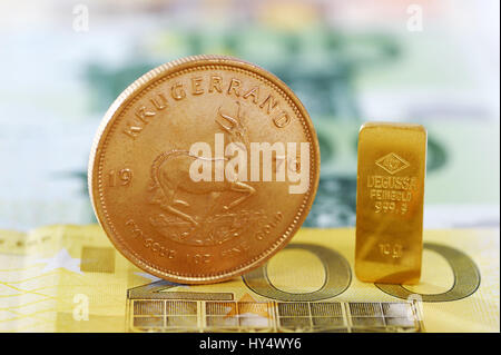 Jug edge coin and gold bar on euro-notes, golden price, Krugerrand-Muenze und Goldbarren auf Euro-Scheinen, Goldpreis - Stock Photo