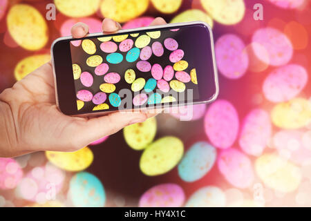 Hand holding mobile phone against white background against colorful easter eggs in wicker basket with flower - Stock Photo
