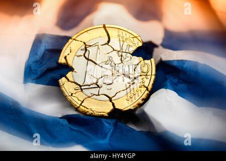 Eurocoin with tears on crumpled Greece flag, symbolic photo debt quarrel, Euromuenze mit Rissen auf zerknitterter - Stock Photo